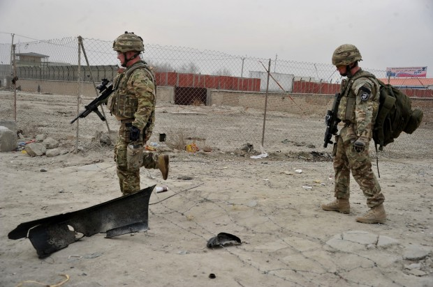 Two US soldiers walk at the site of a suicide attack On the Kabul Jalalabad road, in Kabul on December 27, 2013. A Taliban suicide attacker detonated an explosives-packed car next to a NATO military convoy in Kabul, killing three NATO personnel and injuring at least four civilian passers-by, officials said. The blast in the Afghan capital left the twisted remains of the attacker's car spread across the scene along with several other badly-damaged vehicles, including a NATO sports utility vehicle, witnesses said. (AFP/Noorullah Shirzada)